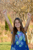 Happy young girl with hands up. Stock Photo