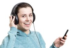 Happy young girl in headphones with player isolated on white bac. Kground. A woman smiles and listens to music from the player. Music in headphones Royalty Free Stock Photos