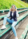 Happy young girl with headphones sitting listens to music Royalty Free Stock Photos