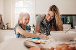 Happy young girl with her mother making dough. Mother and daughter baking in kitchen Royalty Free Stock Images