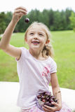 Happy young girl holding bowl full of bing cherries in park Stock Photos