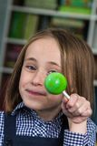 Girl with lollipop. A happy young girl holding a bright green lollipop royalty free stock images