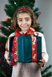 Happy young girl holding christmas present box in front a Christ Stock Photo