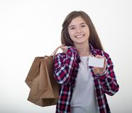 Happy young girl holding discount white card and shopping bags in her hands. Girl with credit card stock image