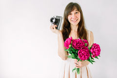 Happy young girl holding in hands bouquet of peony and old vintage camera. Smiling woman, sweet romantic moment. Royalty Free Stock Image