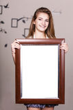 Happy young girl holding portrait frame stock photography