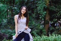Happy young girl holding shirt in her hands in sleeveless t-shirt. Happy young smiling girl holding shirt in her hands wearing sleeveless t-shirt is standing royalty free stock image