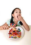 Happy young girl holding spoon eating from dish full of candy lollipop and sugary things Stock Photos