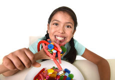 Happy young girl holding spoon eating from dish full of candy lollipop and sugary things Royalty Free Stock Image