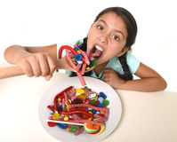 Happy young girl holding spoon eating from dish full of candy lollipop and sugary things Stock Images