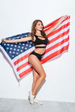 Happy young girl holding USA in bikini. Happy young girl holding USA flag in bikini isolated on a white background Stock Photography