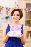 Happy young girl holding wrapped birthday gift Stock Photo