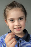 Happy young girl holds her first falling milk teeth Royalty Free Stock Photos