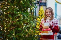 Happy young girl in holiday sweater with pile of Christmas presents royalty free stock photography