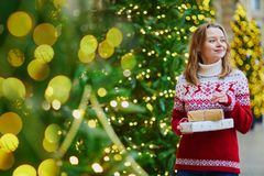 Happy young girl in holiday sweater with pile of Christmas presents stock photo