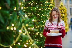 Happy young girl in holiday sweater with pile of Christmas presents stock image