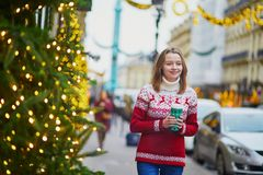 Girl walking with hot drink to go on a street of Paris decorated for Christmas royalty free stock image