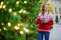 Girl walking with hot drink to go on a street of Paris decorated for Christmas royalty free stock photos