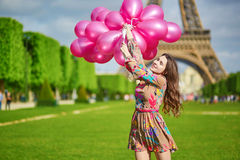 Happy young girl with huge bunch of pink balloons Royalty Free Stock Photos