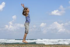 Happy young girl jumping on the beach stock photo