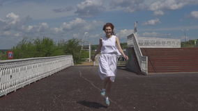 Happy young girl jumping and having fun in summer park. Attractive girl in sunglasses and a white dress walking outdoors stock footage