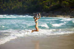 Happy young girl jumping on sea Royalty Free Stock Photos