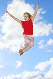Happy young girl jumping. Young girl jumping up in the air against a blue sky with white clouds Stock Photos
