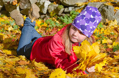 Happy young girl laying on autumn leaves Stock Photos