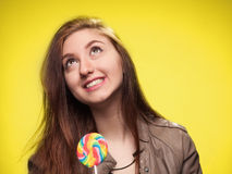 Happy young girl with lollipop on a yellow Stock Image