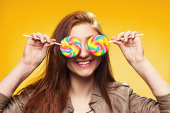 Happy young girl with lollipop on a yellow Royalty Free Stock Photography