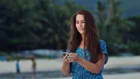 Happy young girl with long hair in a blue dress speaks on the phone on the sunny coast among palms and mountains. Tourist vacation stock footage