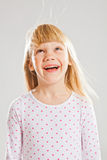 Happy young girl looking up. Studio portrait of happy smiling young girl looking up with wind blowing her hair Royalty Free Stock Images