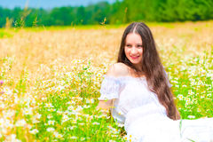 Happy young girl lying in a field with daisies Stock Photography