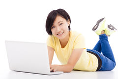Happy young girl lying on the floor with a laptop Stock Photos
