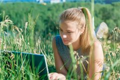 Happy young girl lying on the grass and looking at the laptop monitor. Read the messages on the laptop.  royalty free stock photos