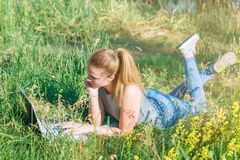 Happy young girl lying on the grass and looking at the laptop monitor. Read the messages on the laptop.  stock photo