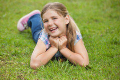 Happy young girl lying on grass at park Stock Images