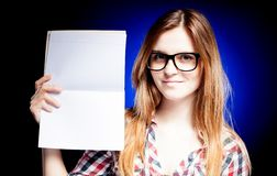 Happy young girl with nerd glasses holding exercise book Stock Image