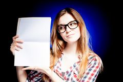 Happy young girl with nerd glasses holding exercise book. Happy young girl with nerd glasses holding open exercise book Royalty Free Stock Images