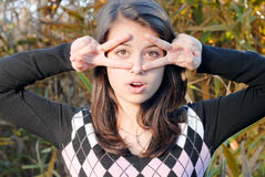 Happy young girl outdoors showing glasses sign Royalty Free Stock Photo