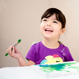 Happy young girl painting a picture. Toddler laughing as she paints a picture on a canvas Stock Photography