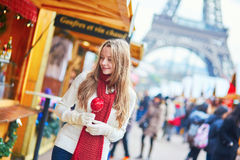 Happy young girl on a Parisian Christmas market. Happy young girl with caramel apple on a Parisian Christmas market with the Eiffel tower in the background Royalty Free Stock Image