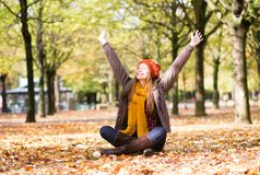 Happy young girl in park on a fall day Stock Photos