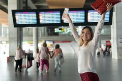 Happy young girl with passport and ticket stands and raised her hands up. On the background of scoreboard with the notice Stock Photography