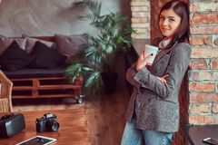 Portrait of a young girl photographer dressed in a gray elegant jacket holding cup of takeaway coffee while leaning on a. Happy young girl photographer dressed royalty free stock images