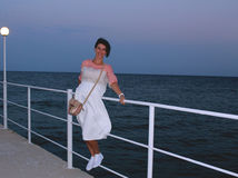 Happy young girl on the pier. Young woman with dark hair bob dressed white skirt and white gumshoes stands evening on the pier Stock Photo