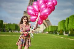 Happy young girl with pink balloons in Paris Stock Photos