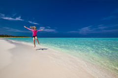 Happy young girl in pink top jumping on exotic beach, Maldives stock images