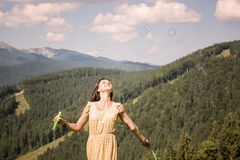 Happy young girl playing with soap bubbles. Beautiful happy young girl playing with soap bubbles royalty free stock photos