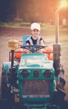 Happy young girl plays on  tractor outdoors in the garden Stock Image